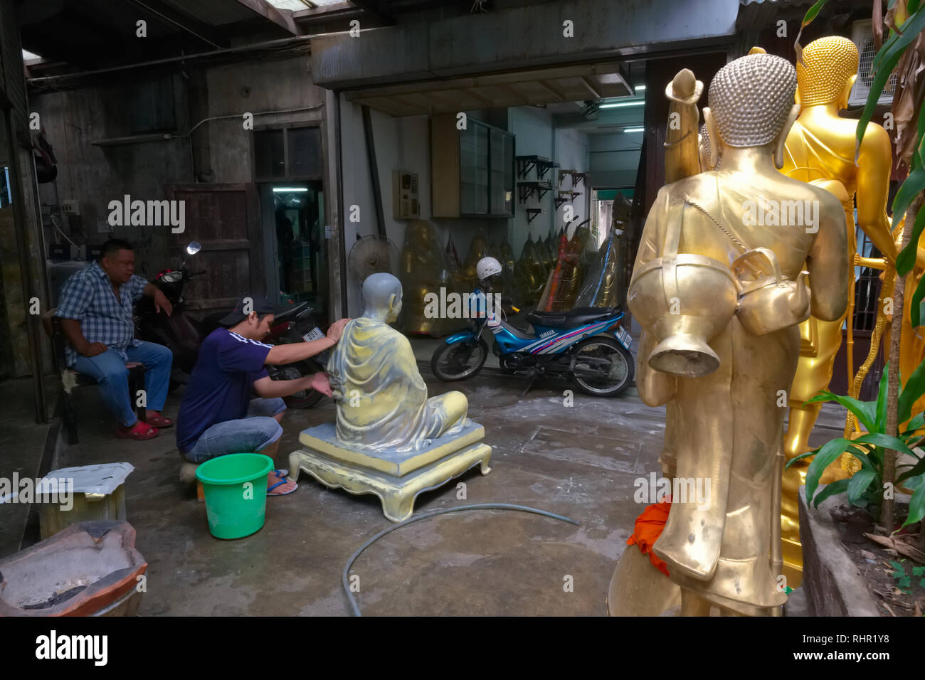 A craftsman in a backstreet off Bamrung Muang Rd. in Bangkok, Thailand, puts finishing touches to the statue of a revered Buddhist monk - Stock Image
