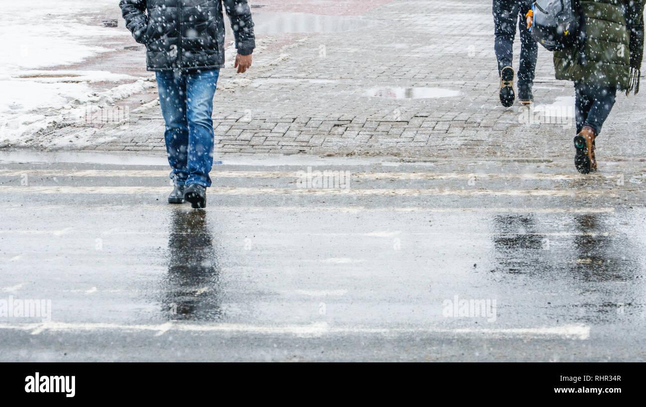 Winter City Slippery Sidewalk. Feet of people walking along the icy snowy pavement in crosswalk in snowfall. Pair of shoe on icy road in winter. Abstr - Stock Image