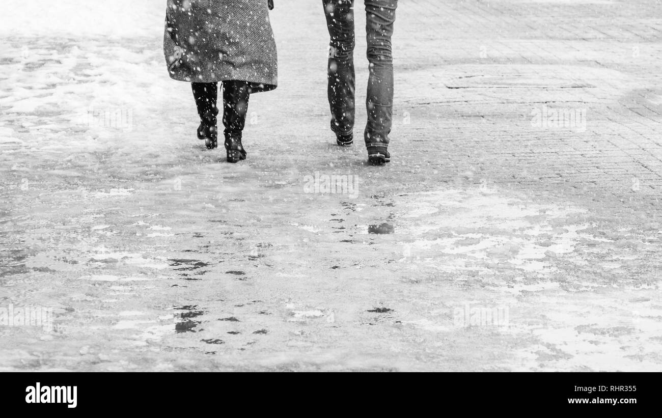 Winter City Slippery Sidewalk. Back view on the feet of people walking along the icy snowy pavement. Pair of shoe on icy road in winter. Abstract empt - Stock Image