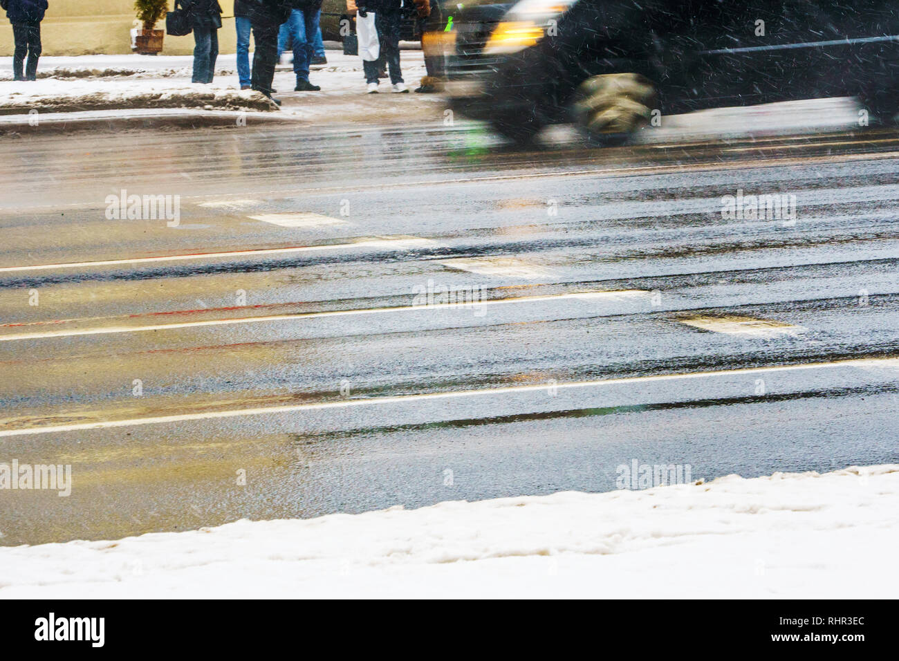 Crosswalk. Slippery wet asphalt city road in winter. Driving cars are blurred in motion. Waiting for the resolving light of the traffic light concept - Stock Image