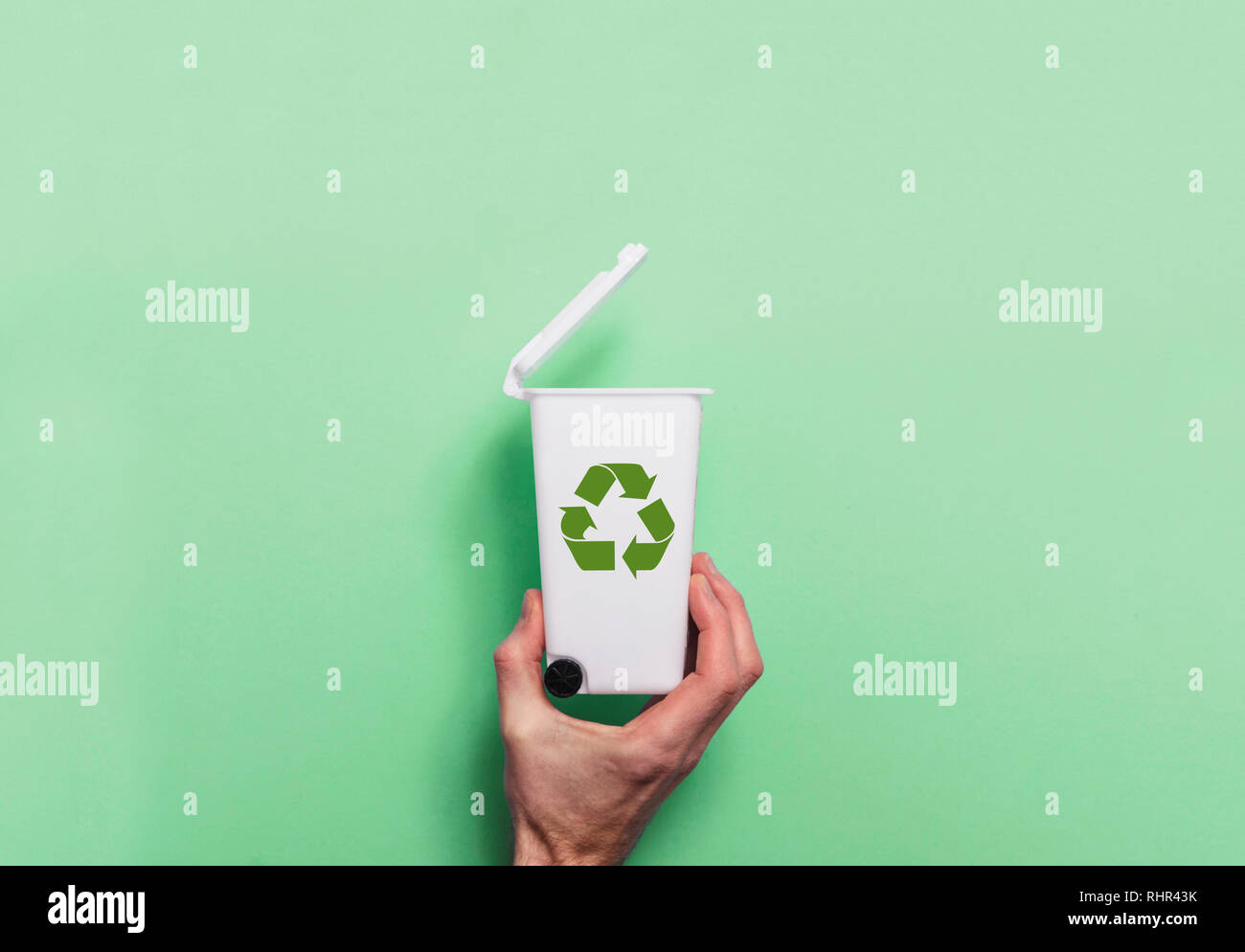 Hand holding recycling rubbish bin against a green background - Stock Image
