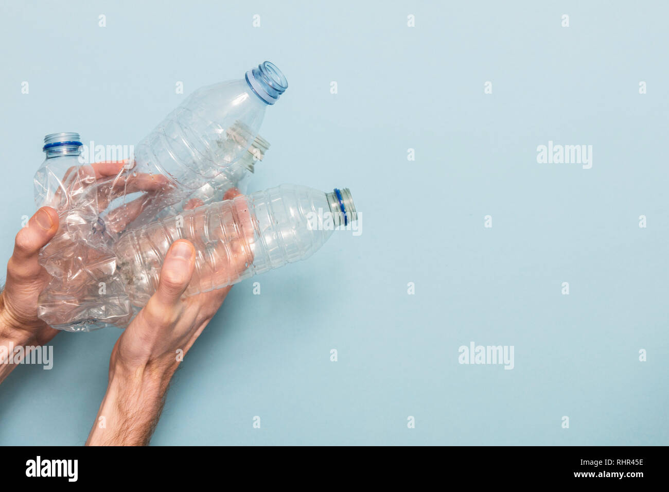Hand holding empty plastic bottle recycling against a blue background - Stock Image