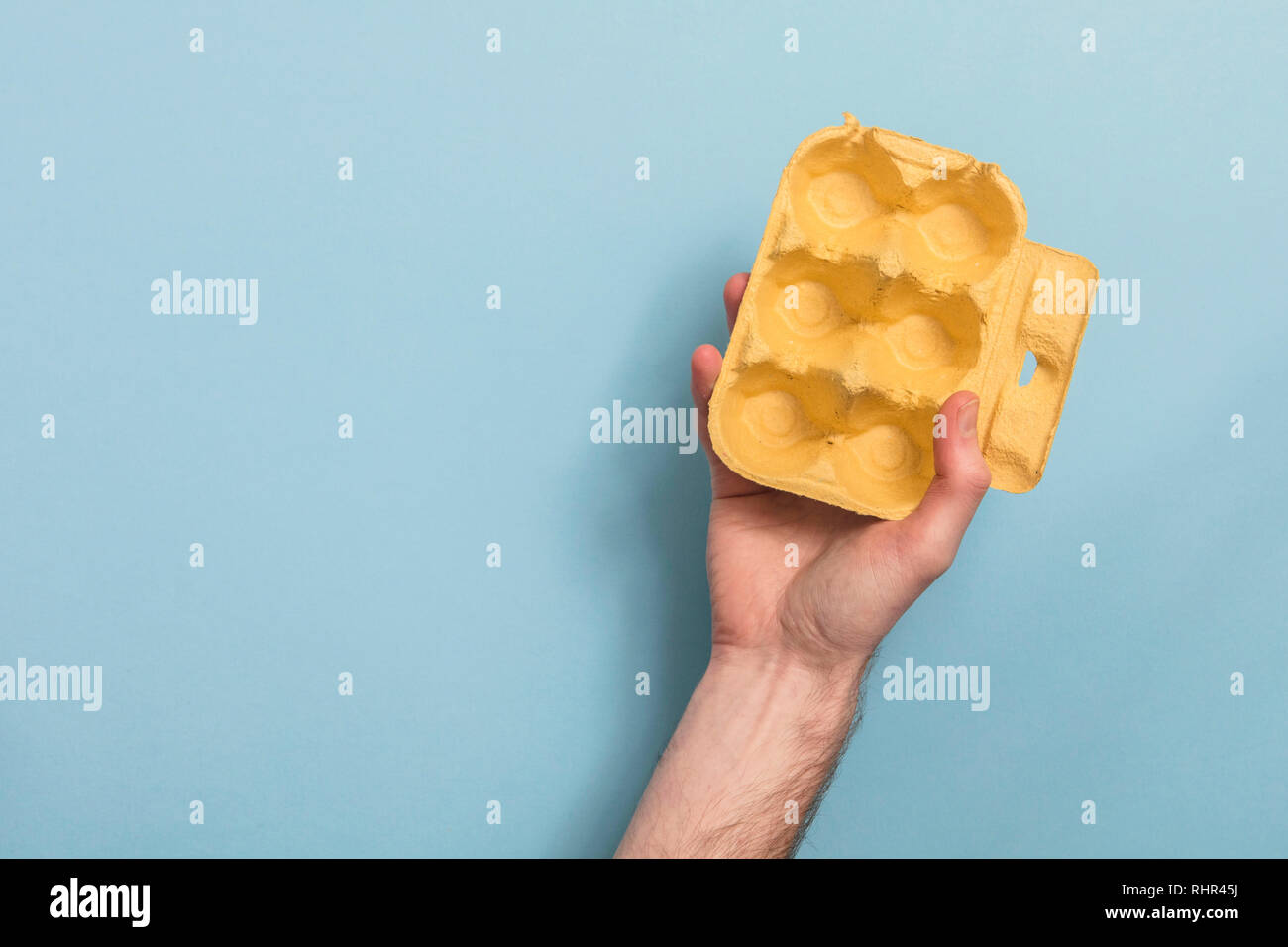 Hand holding empty egg box recycling rubbish - Stock Image