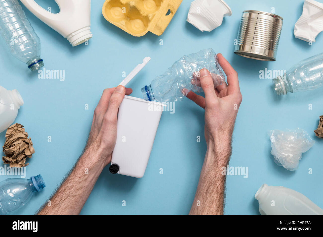 Hand holding a recycling garbage bin with lots of waste packaging - Stock Image