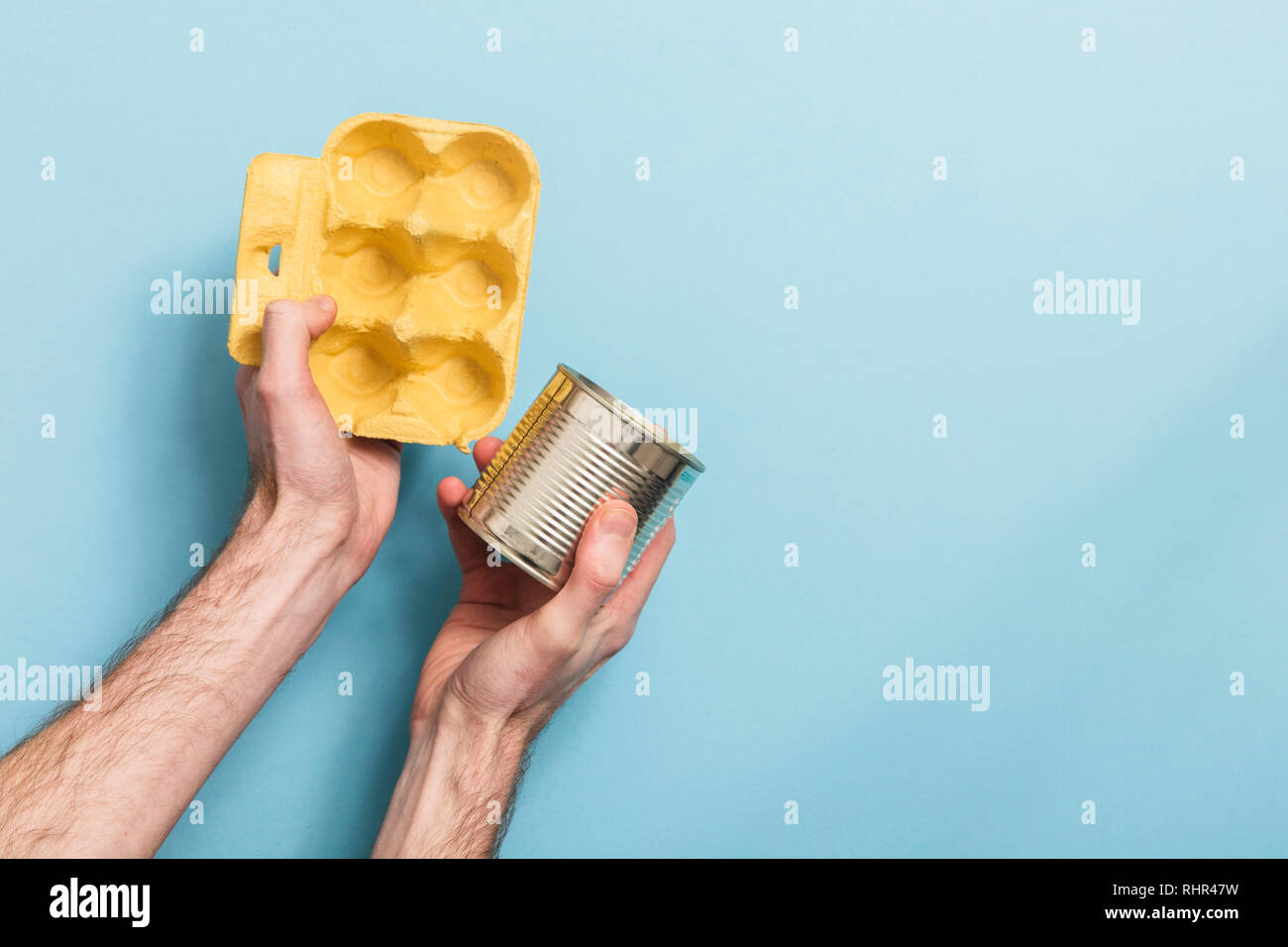 Hand holding recycling rubbish against a blue background - Stock Image