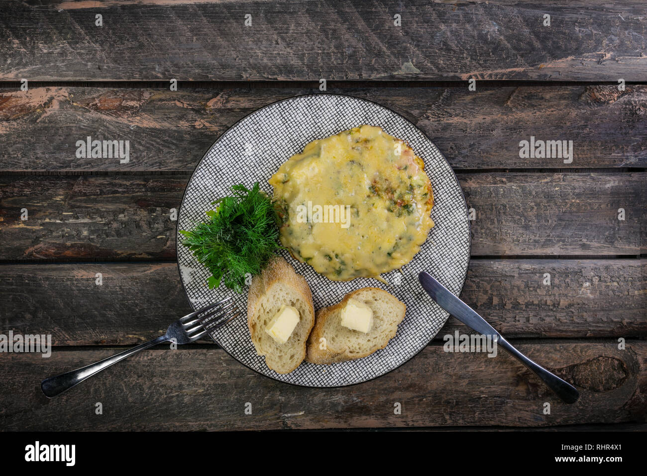 Omelet with tomatoes, zucchini and mushrooms served by cutlery. Omelette breakfast. Healthy food. Top view. - Stock Image