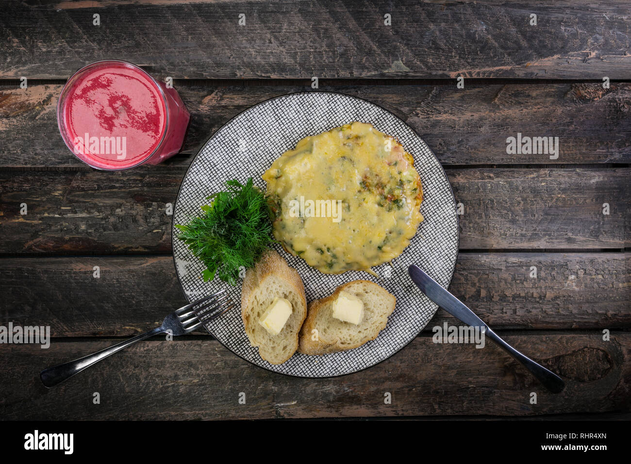 Omelet with tomatoes, zucchini and mushrooms served by cutlery and fresh berry drink. Omelette breakfast. Healthy food. Top view. - Stock Image