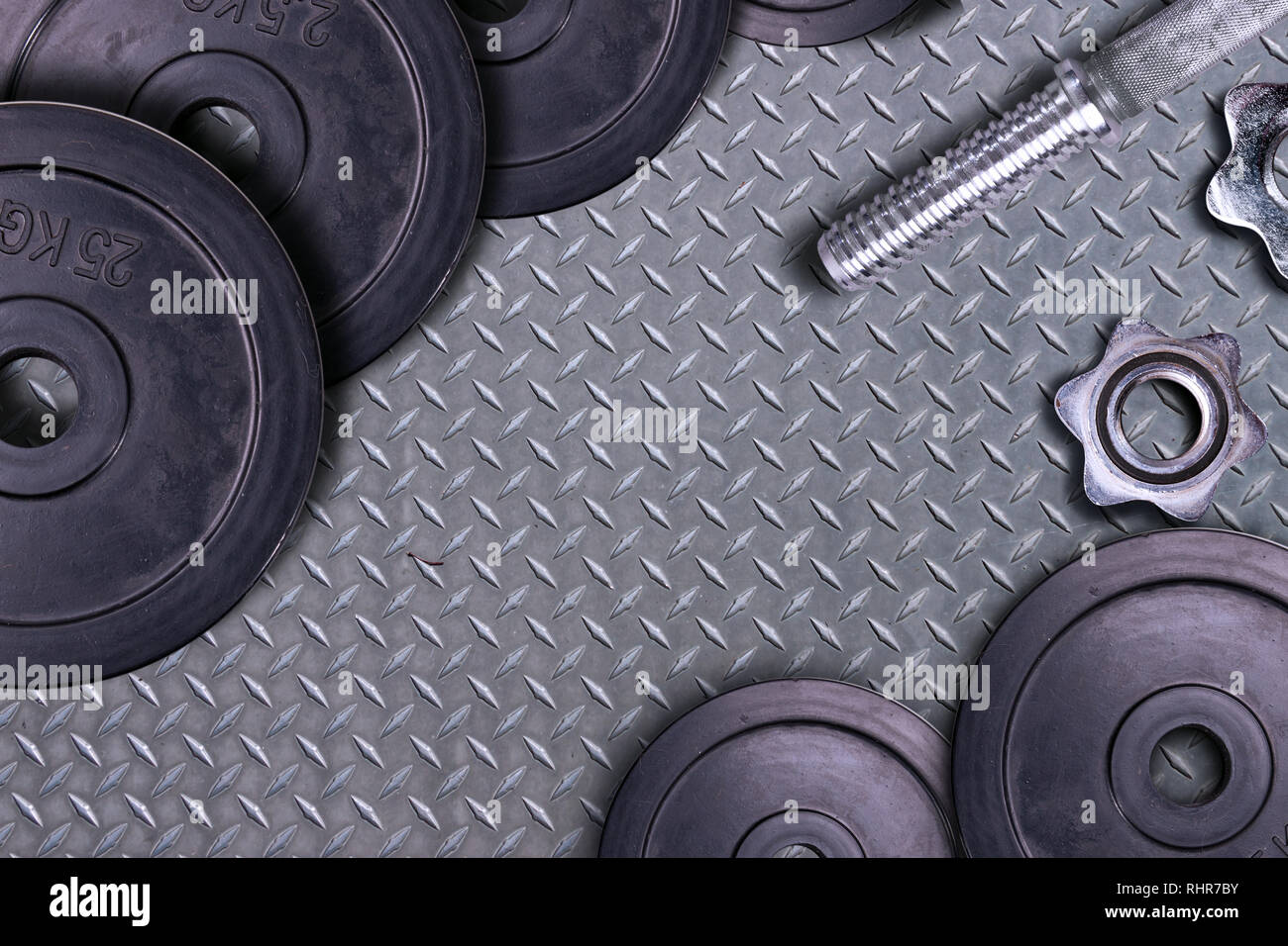 Dumbbells on carbon background. Dumbbells and weights are lying on the floor in the gym. Barbell set and gym equipment. Metal loads in the fitness clu - Stock Image