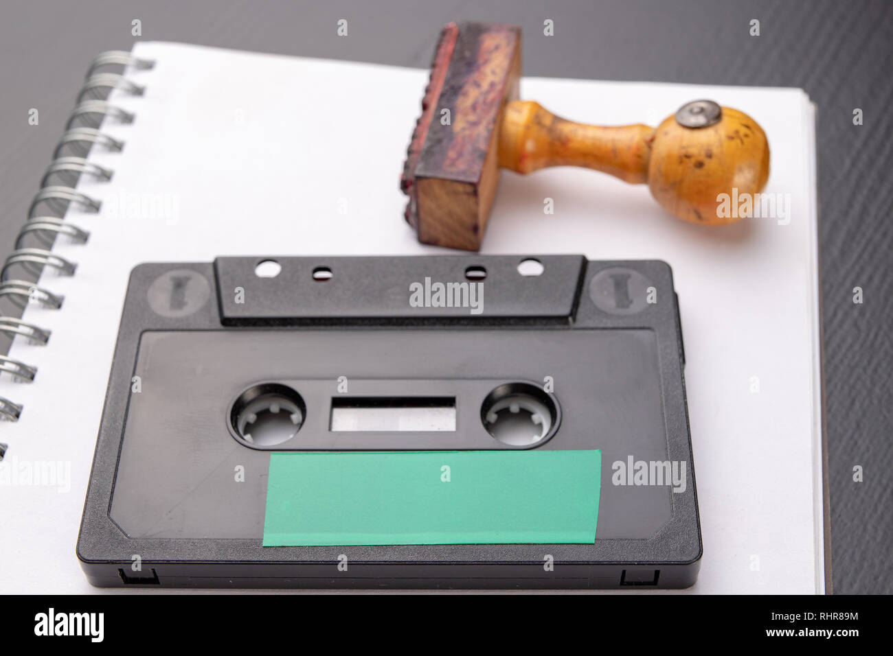 Old wooden rubber stamp and audio cassette on a white piece