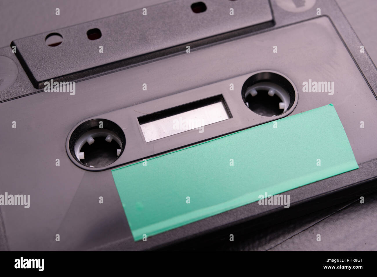 Audio cassette with space for text entry. Cassette without description. Dark background. - Stock Image
