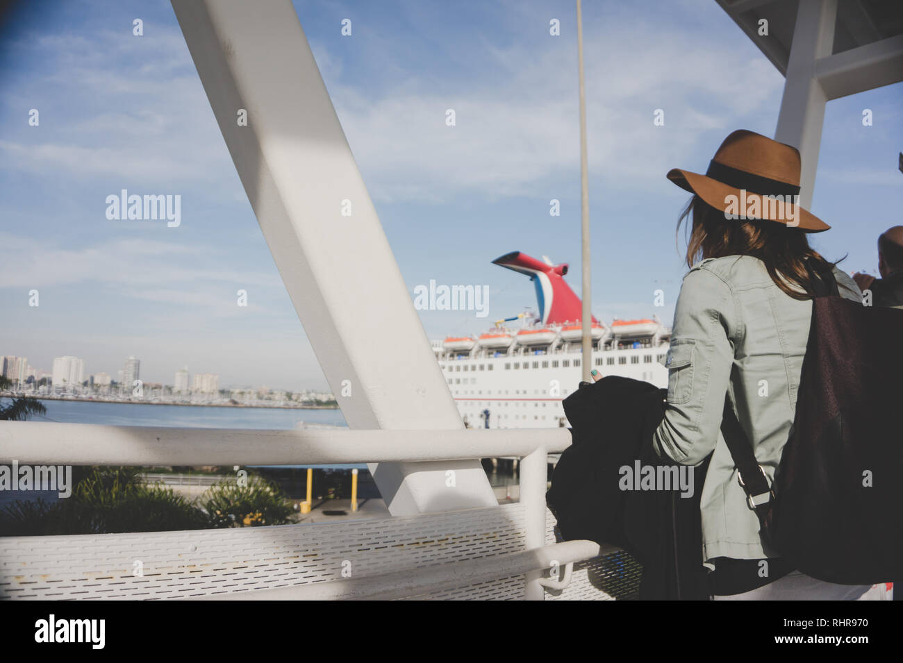 A young woman in a brown hat boards the Carnival Inspiration cruise ship in Long Beach, California, USA via the gangway onto the boat on a sunny day - Stock Image