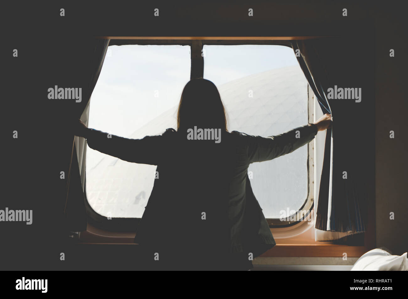 Pretty woman viewed from the back excitedly opening curtains of her cabin on a cruise ship (This is the Carnival Inspiration - California) - Stock Image