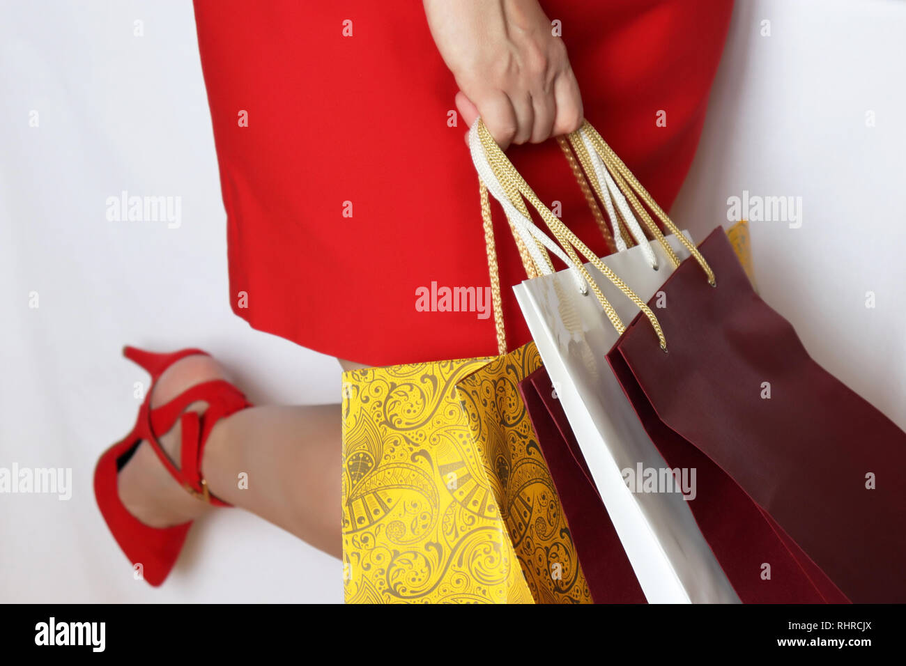 Woman with shopping bags isolated on white background. Girl in red dress and shoes on high heels, concept of shopping, sale and gifts - Stock Image