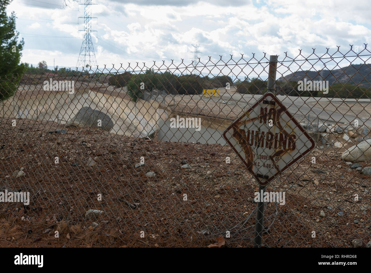 Rusty no dumping sign on fence in front of storm channels in Claremont California - Stock Image