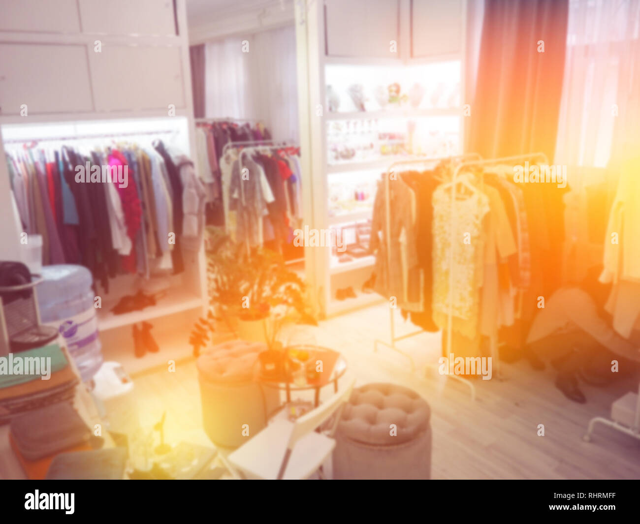 blurred clothes on hanger in clothing store. Abstract blur and defocused shopping mall of department store interior for background. Stock Photo
