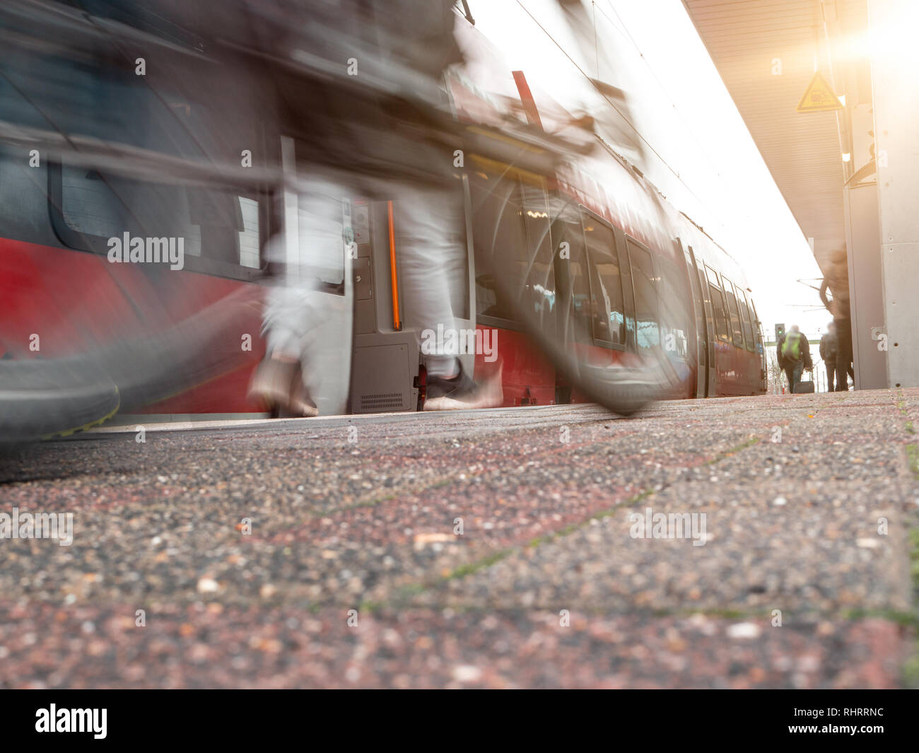 rail platform with red commuter train in motion blur in Cologne, Germany. man with mike blurred in foreground - Stock Image