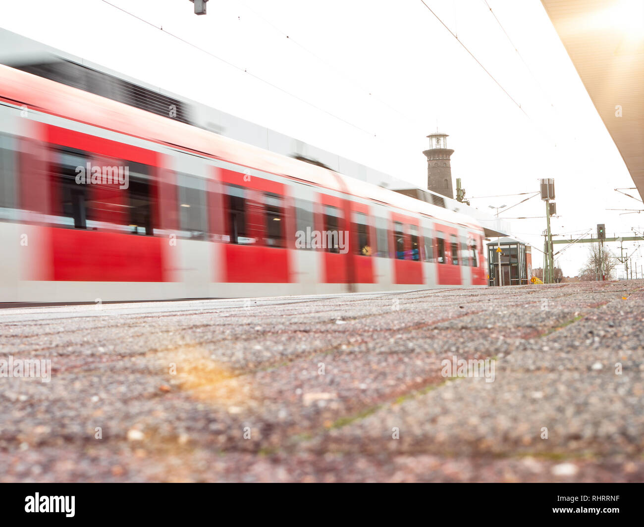 rail platform with red commuter train in motion blur in Cologne, Germany. - Stock Image
