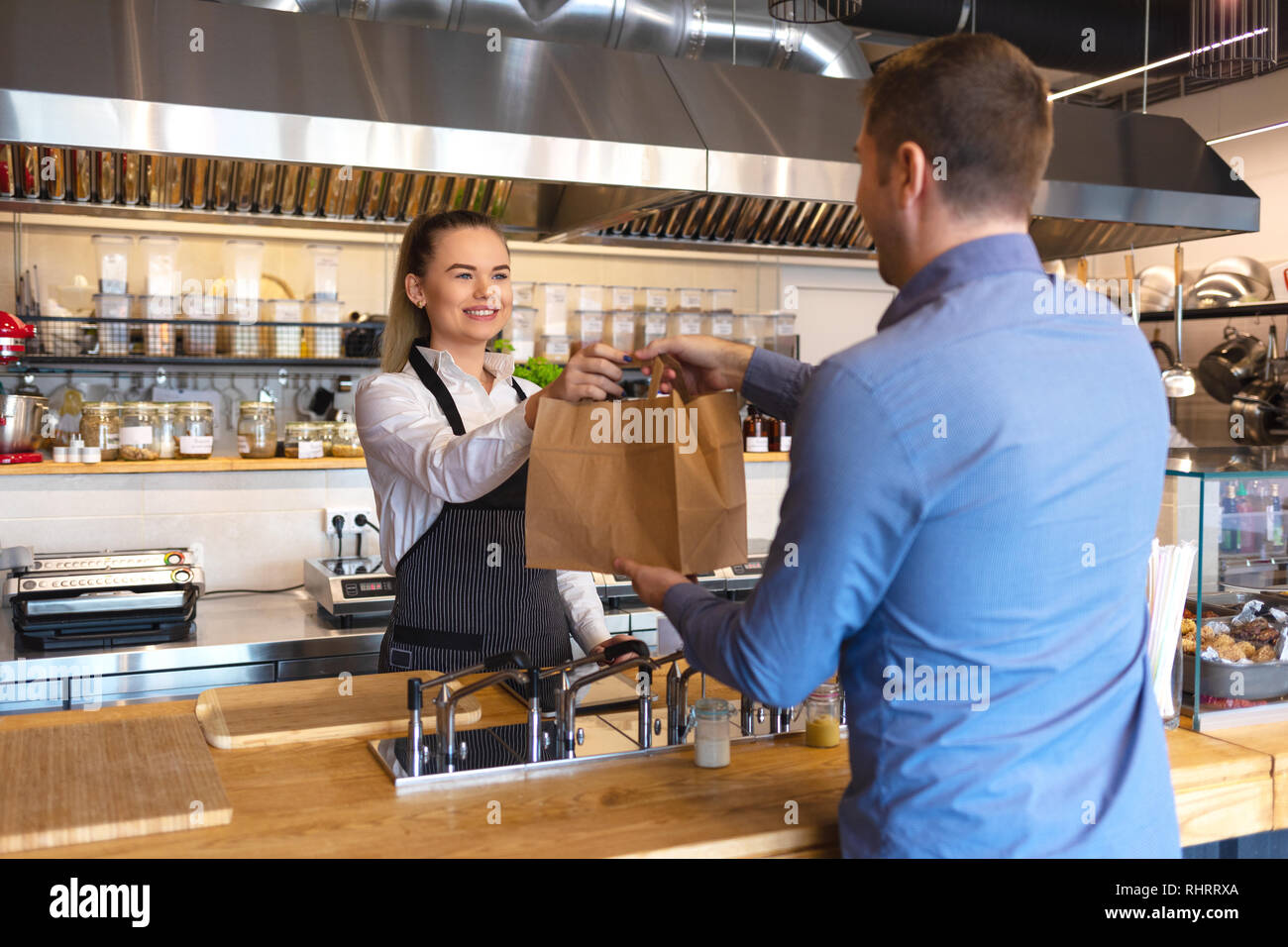 Small business and entrepreneur concept with smiling young waitress with black apron serving customer at counter in family restaurant, takeaway food - Stock Image