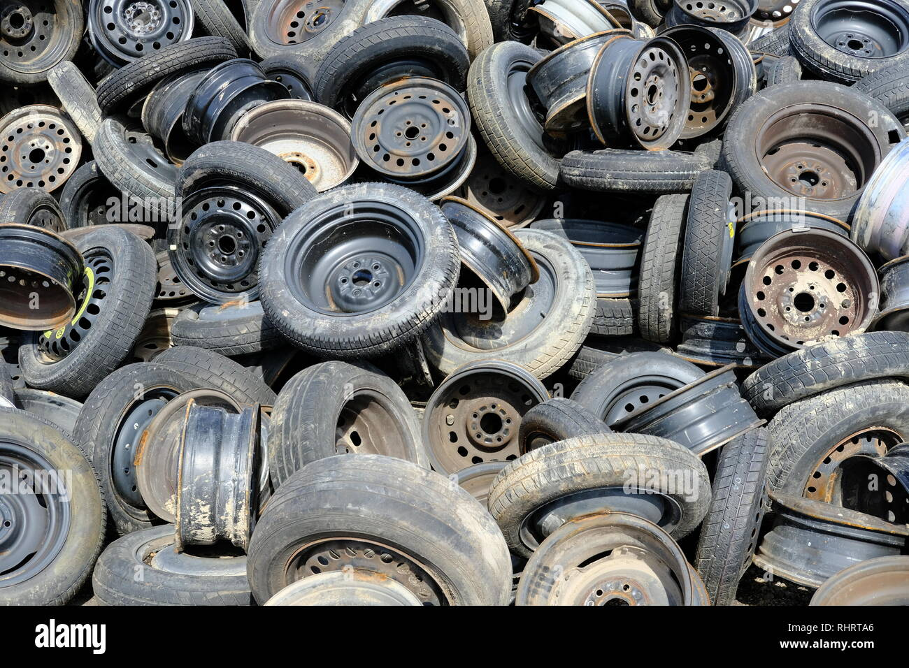 Randomly placed used or discarded tires with rims or wheels