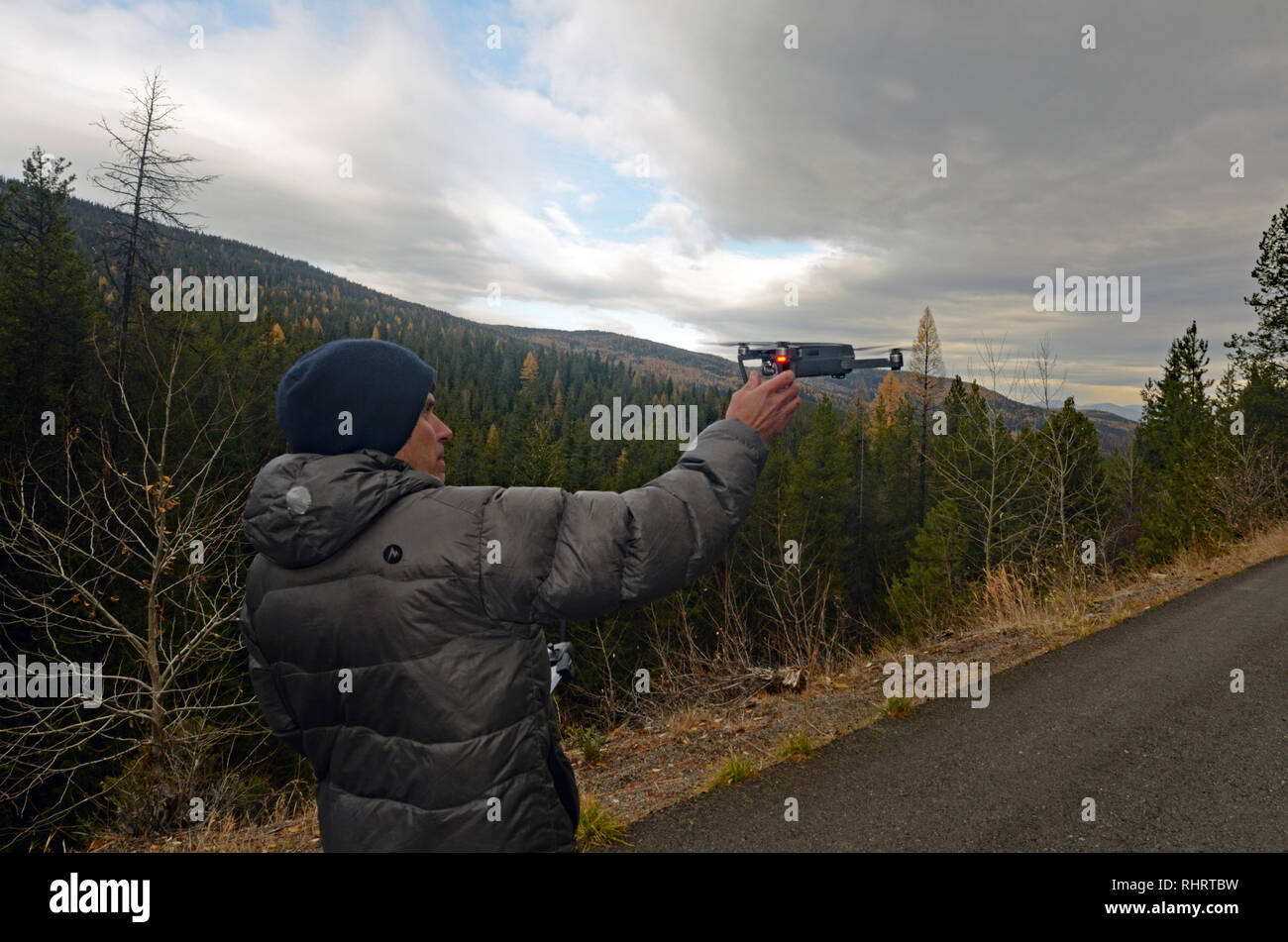 Filmmaker Scott Rulander operates a DJI Mavic Pro drone during a videography session in the Purcell Mountains, northwest Montana. - Stock Image
