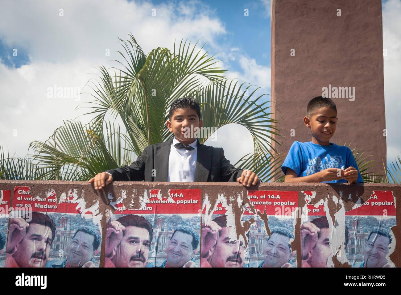 Caracas, Dtto Capital / Venezuela - 03/05/2013. Two boys smile and some Nicolas Maduro and Hugo Chávez political propaganda in Catia neighborhood. - Stock Image