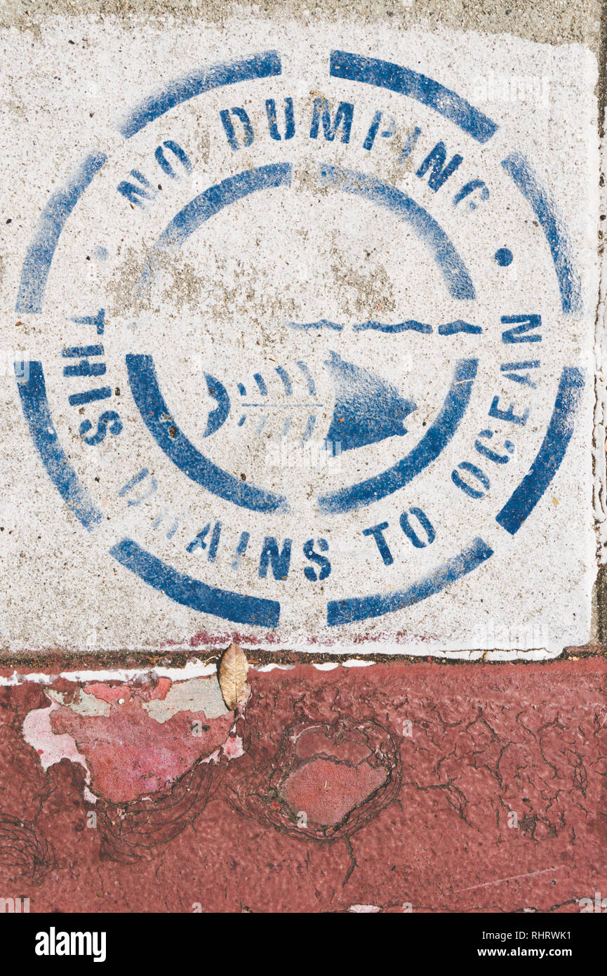 Sign above storm drain in Los Angeles, California which says 'No Dumping. This drains to ocean.' - Stock Image