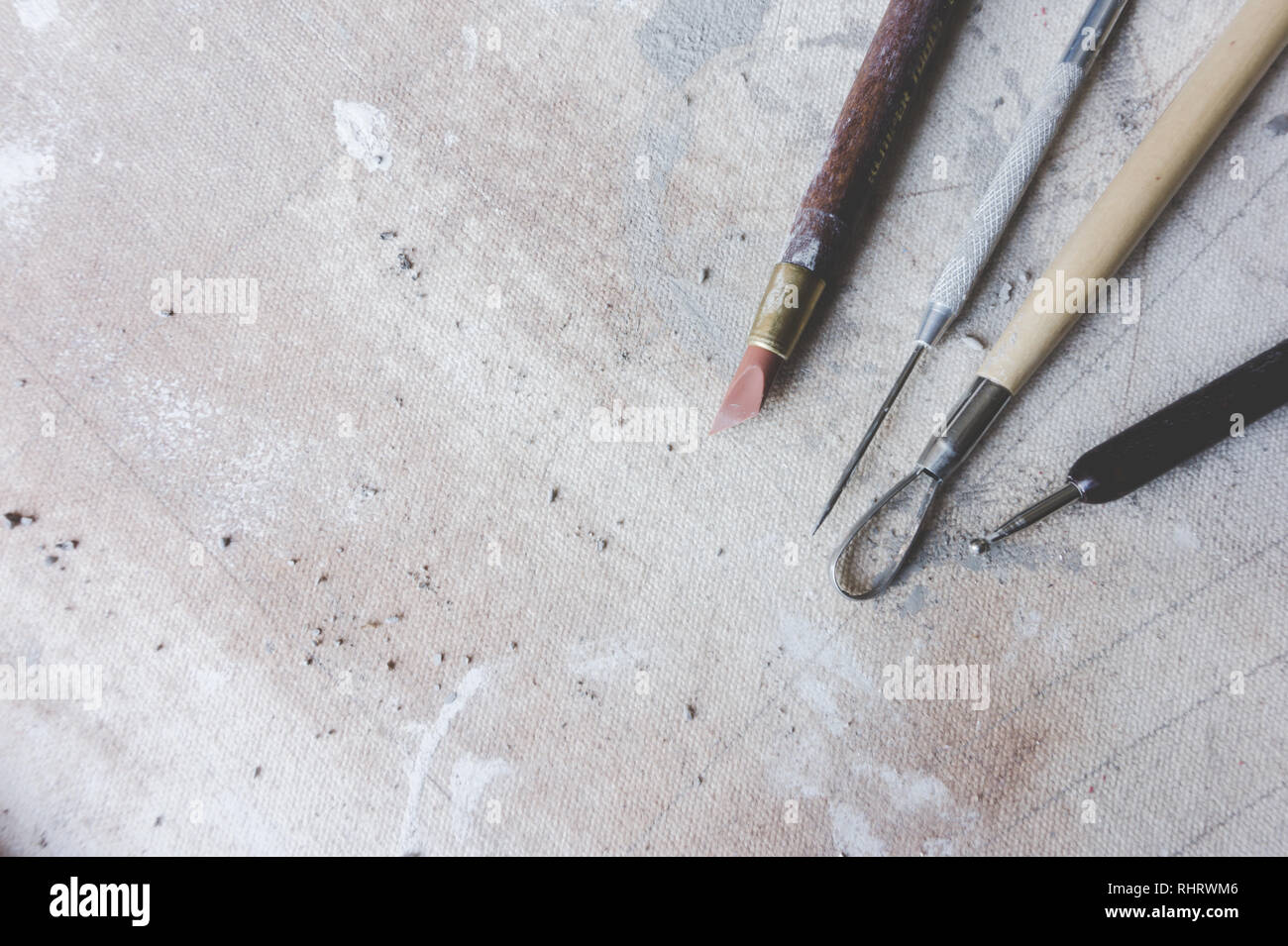 Close up view from above of typical ceramics tools / art supplies in a ceramic art studio - Stock Image