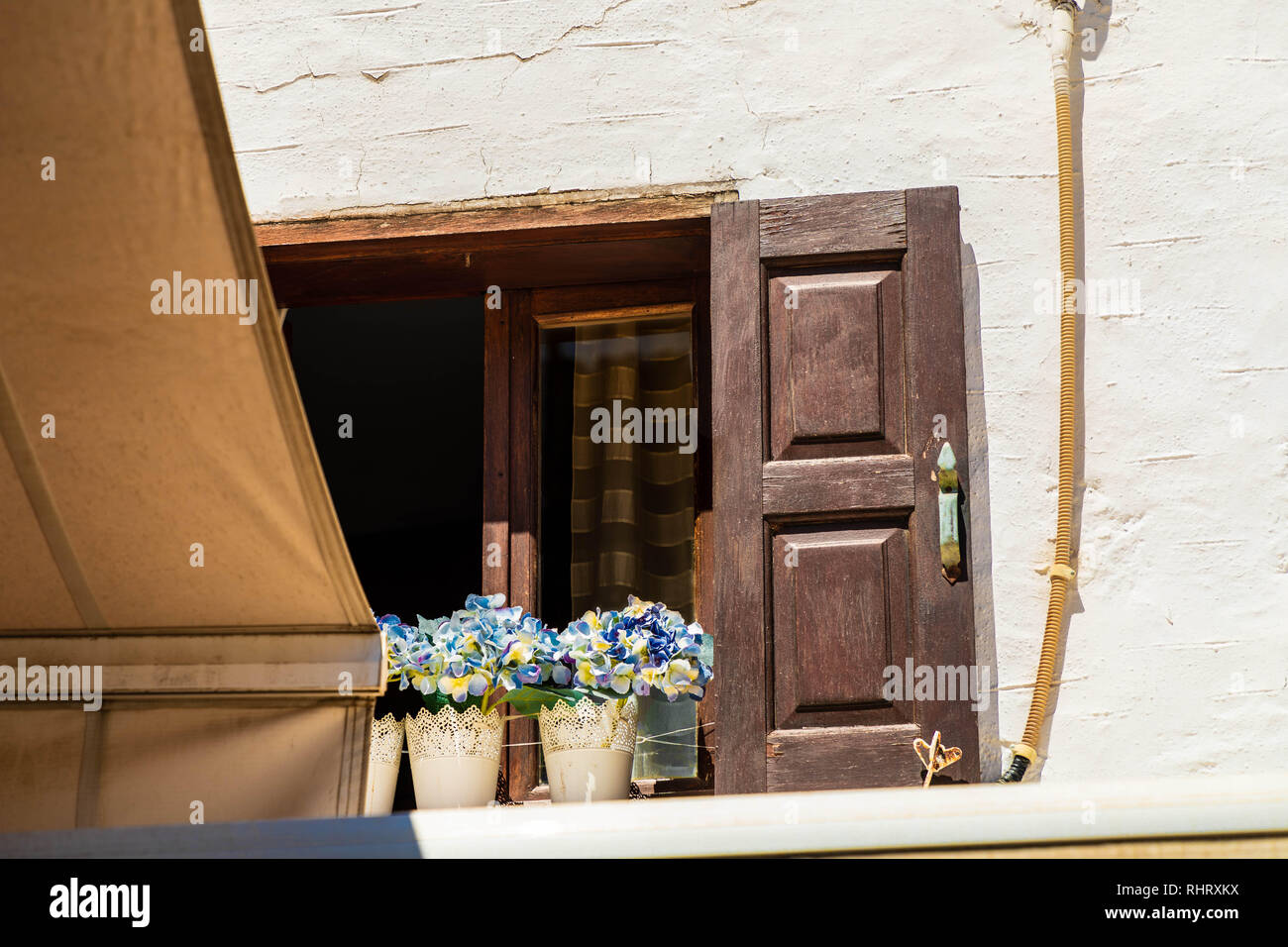 Upper apartment in Lindos Village with silk flowers in lace pots on the window sills. - Stock Image
