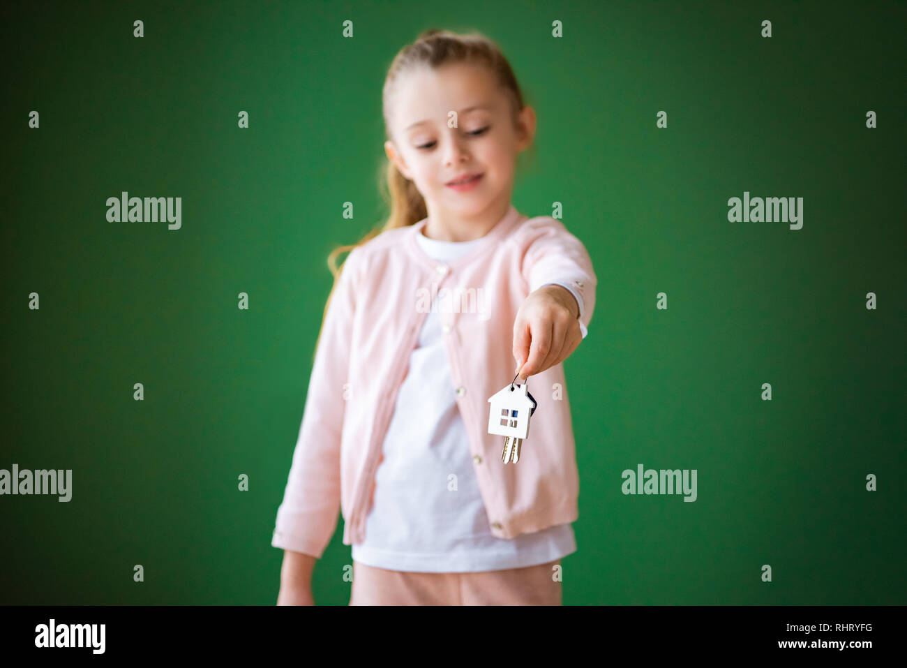 selective focus of kid holding house shaped key chain on green background - Stock Image