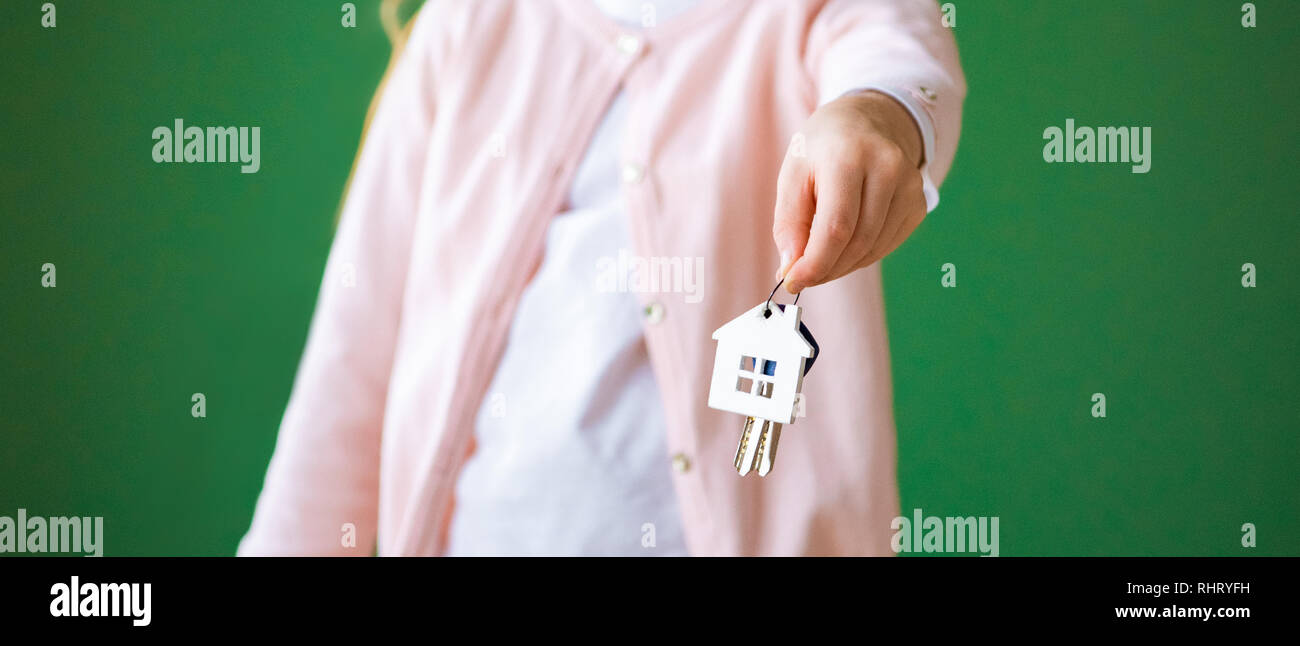 cropped view of kid holding house shaped key chain isolated on green - Stock Image