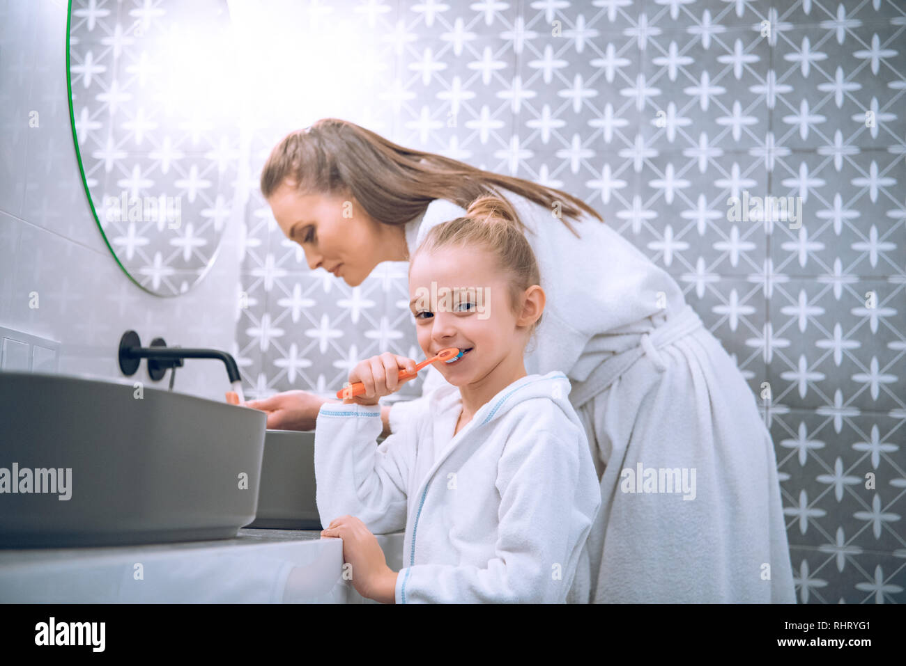 a3e6bbf6c1 cute kid brushing teeth near mother in bath robe Stock Photo ...