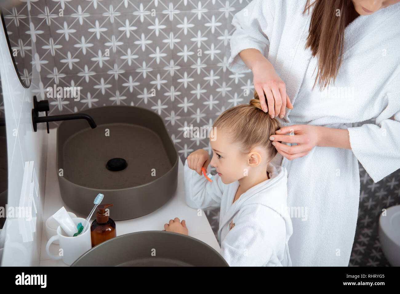 ef2cd3ca69 cropped view of mother touching hair of cute daughter brushing teeth in bath  robe