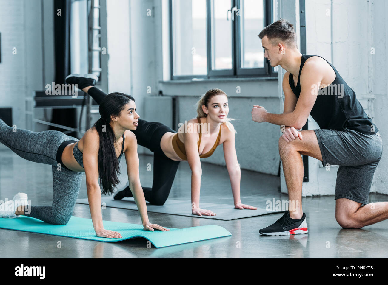 handsome male trainer looking at athletic multiethnic girls in sportswear exercising on yoga mats in gym - Stock Image