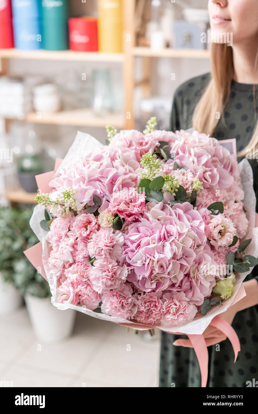 beautiful fresh cut bouquet of mixed flowers in woman hand. the work of the florist at a flower shop. Delicate Pastel tones color Stock Photo