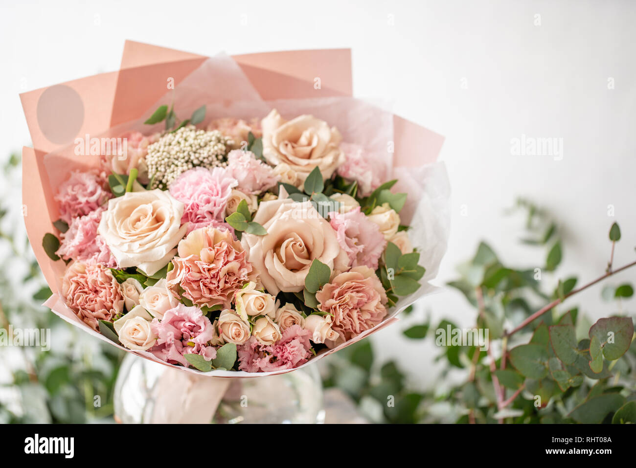 beautiful fresh cut bouquet of mixed flowers in vase on wooden table. The work of the florist at a flower shop. Delicate Pastel tones color Stock Photo