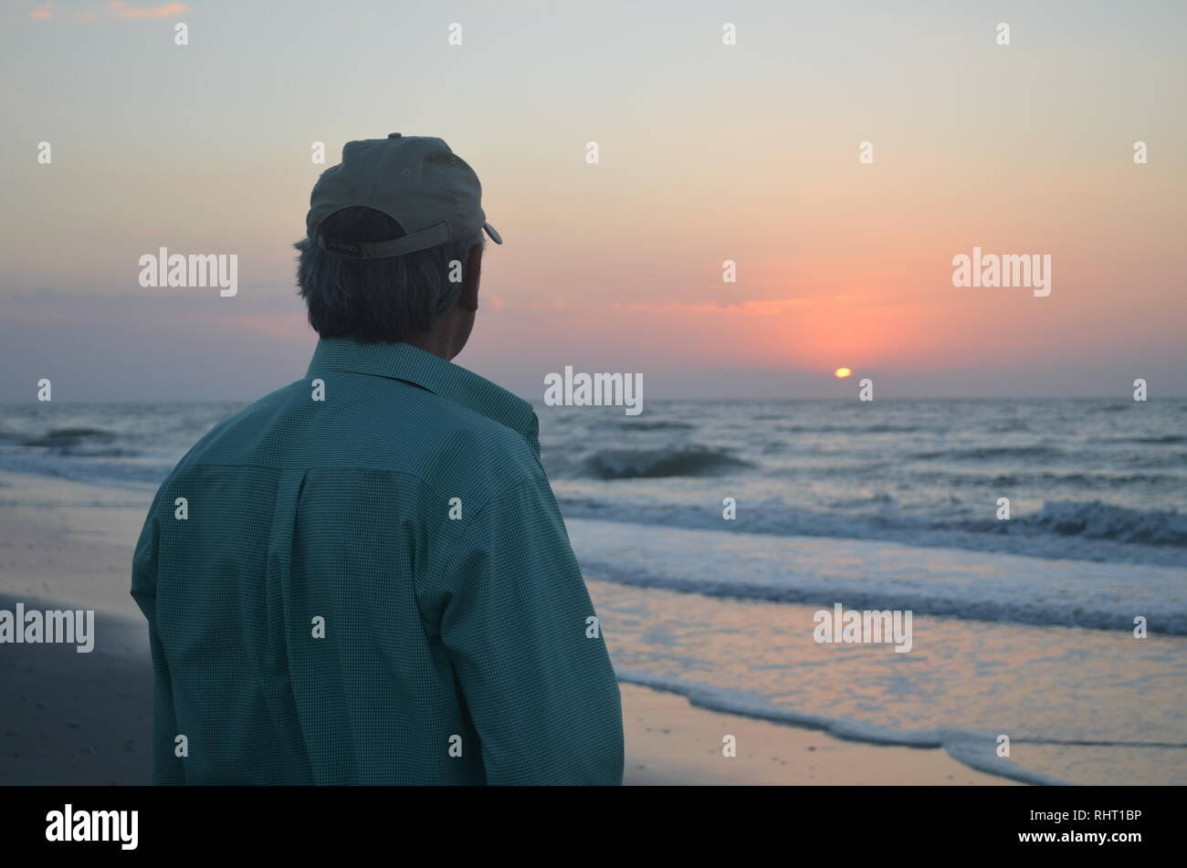 Man watching sunrise on U,S. East Coast - Stock Image