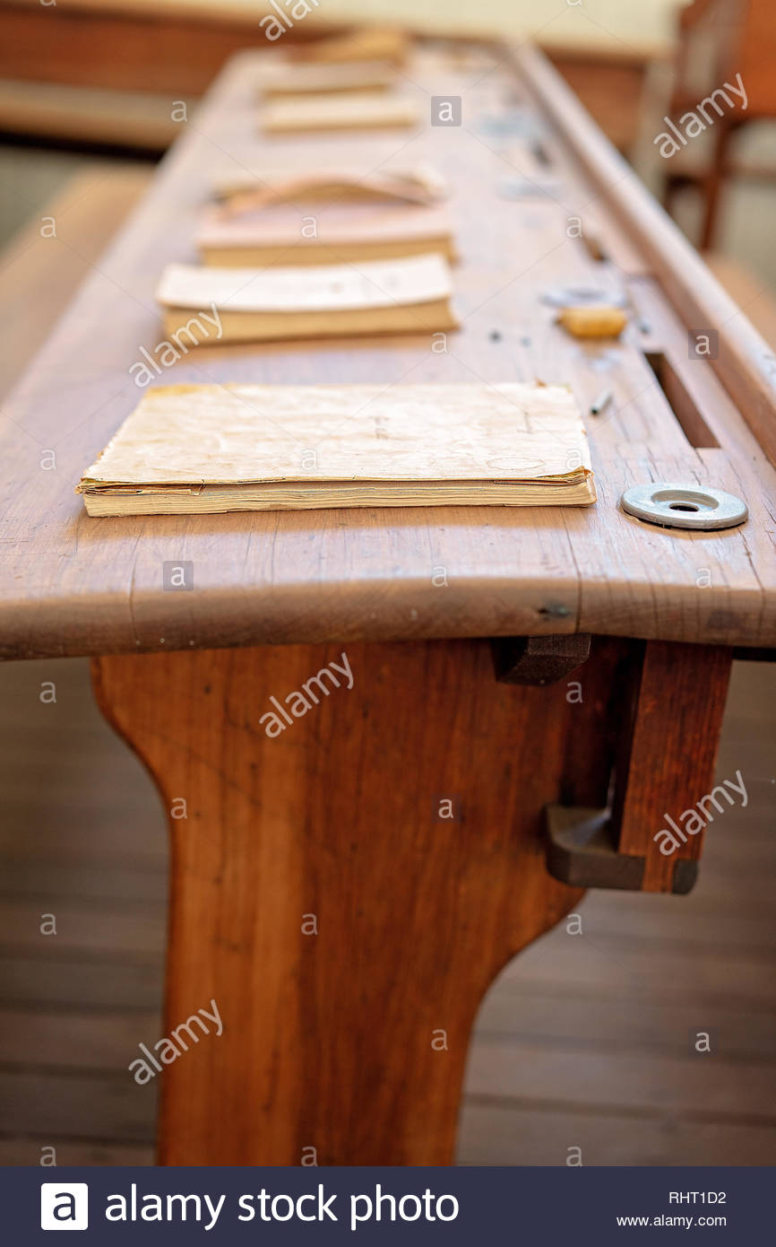 Vintage wooden student form desk with inkwell and books as used in a school room in yesteryear Stock Photo