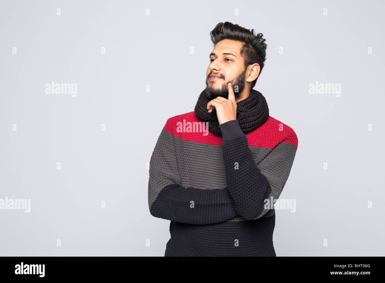 Handsome indian man wearing sweater over isolated gray background with hand on chin thinking about question, pensive expression. Stock Photo
