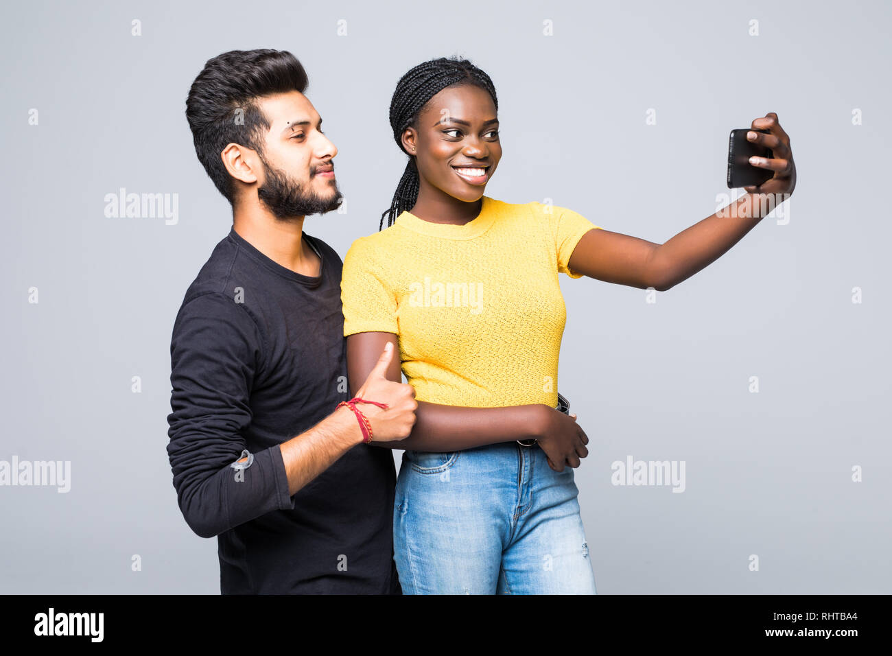 Young interracial couple, indian man and african woman taking selfie on mobile phone isolated on white background - Stock Image