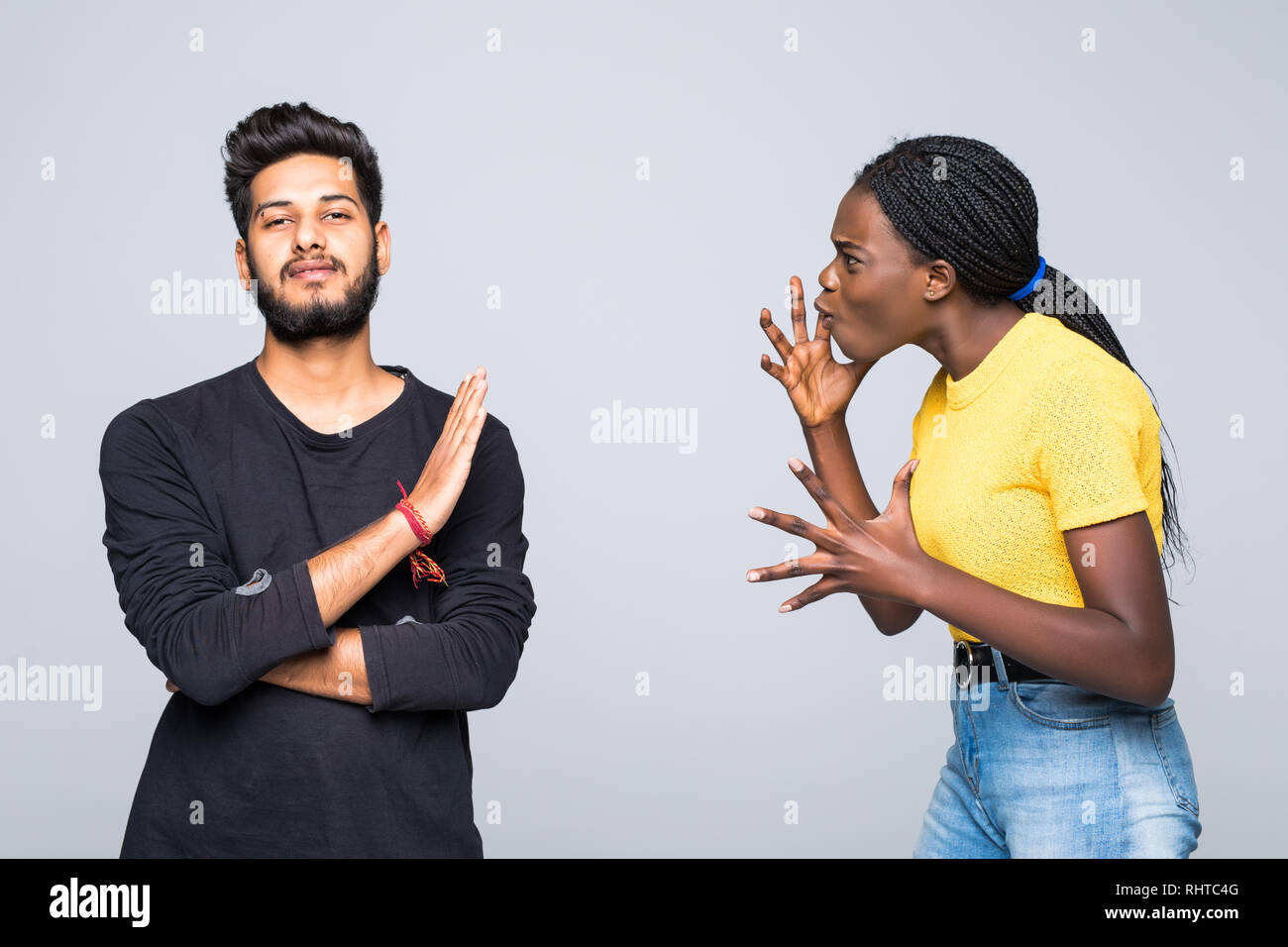 Portrait of mixed race couple sort out relationships, look in displeasure at each other, have quarrel stand against white background. Interracial fami Stock Photo