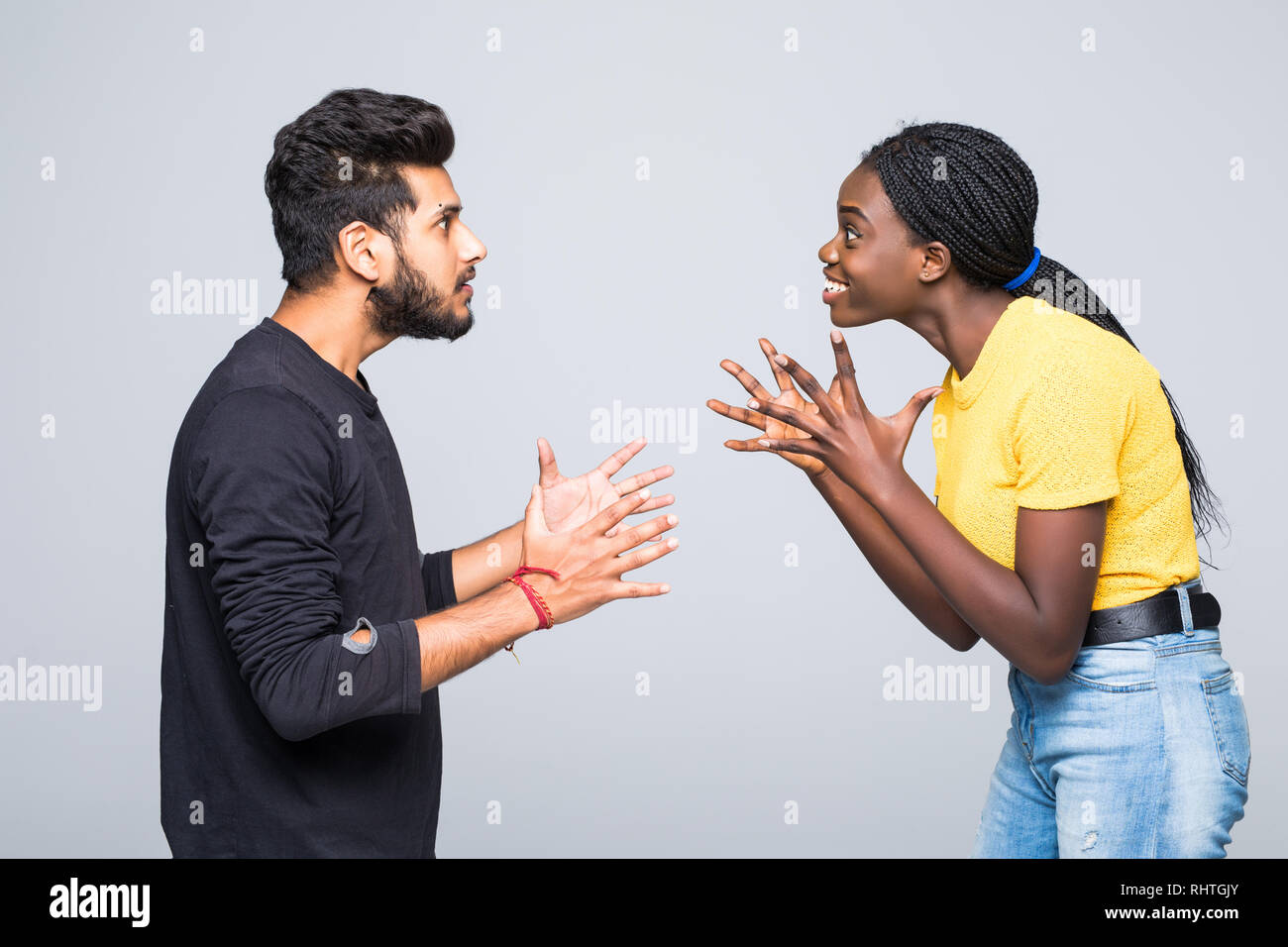 Excited surprised young interracial couple dressed in identical clothes and eyeglasses keeping clenched fists at their faces, screaming, opening mouth Stock Photo
