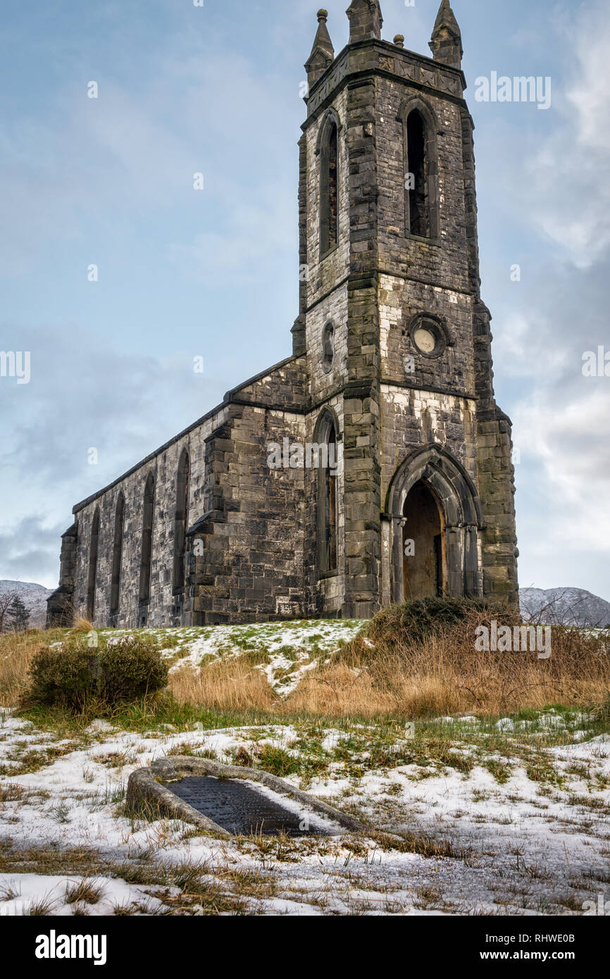 This is a picture  of the ruins of Dunlewy Church at the base of Errigal Mountain in Donegal Ireland. There is an over turned grave stone in the forgr - Stock Image