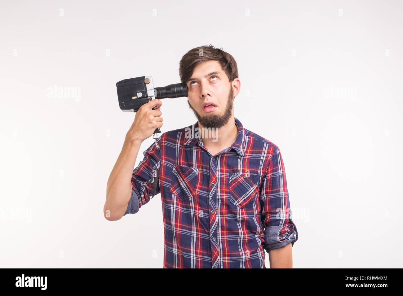 Joke, photo and gesture concept - young funny silly man posing with camera near his head on white background - Stock Image