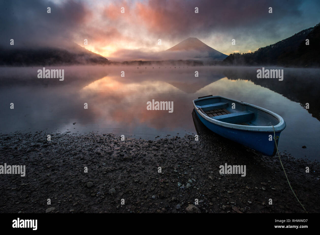 fishing boats on the shore of Lake Shōji with morning mist and Mount Fuji at sunrise - Stock Image