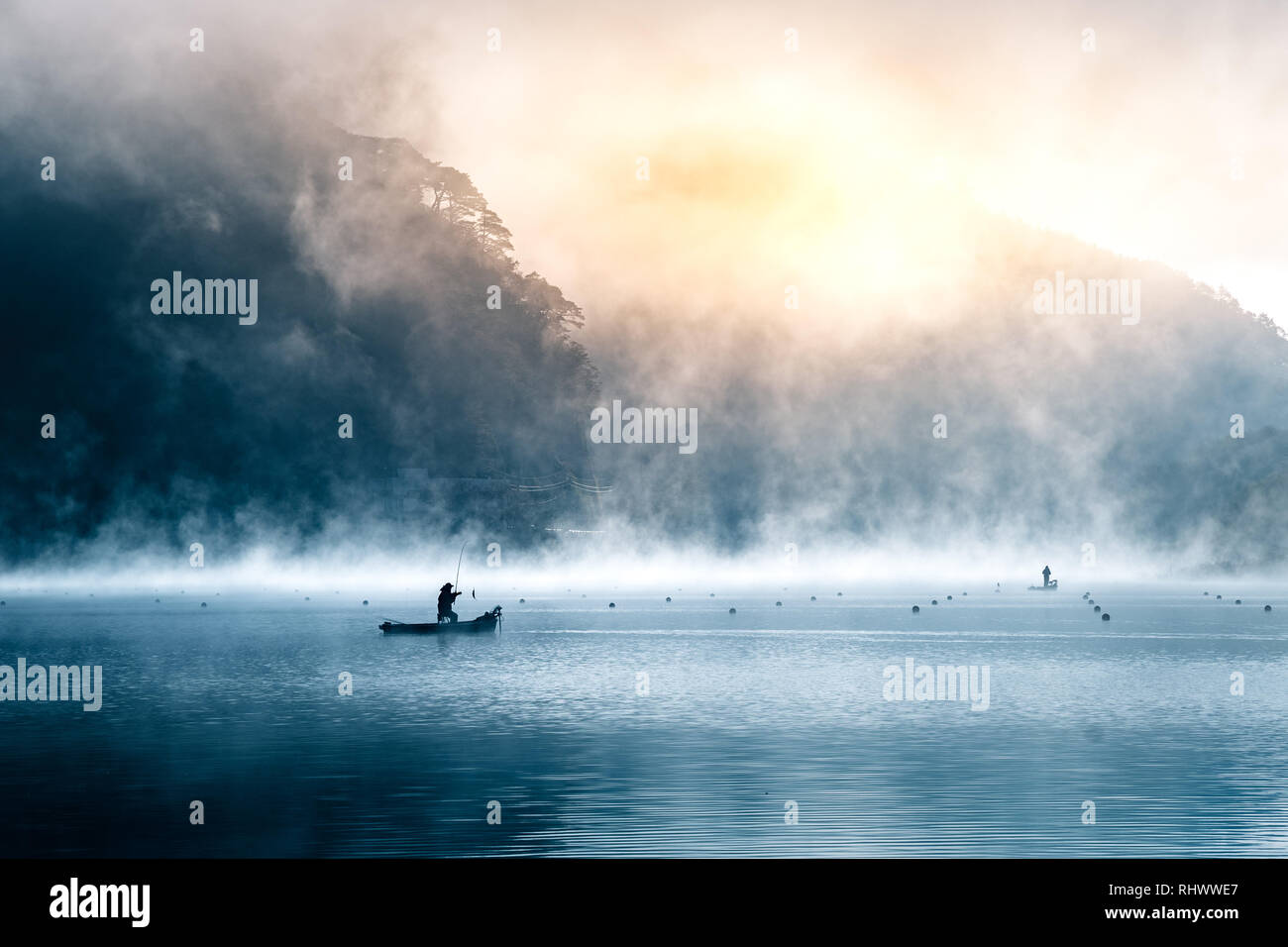 the silhouette of a fisher man with his boat on a misty moring at Lake Shoji - Stock Image