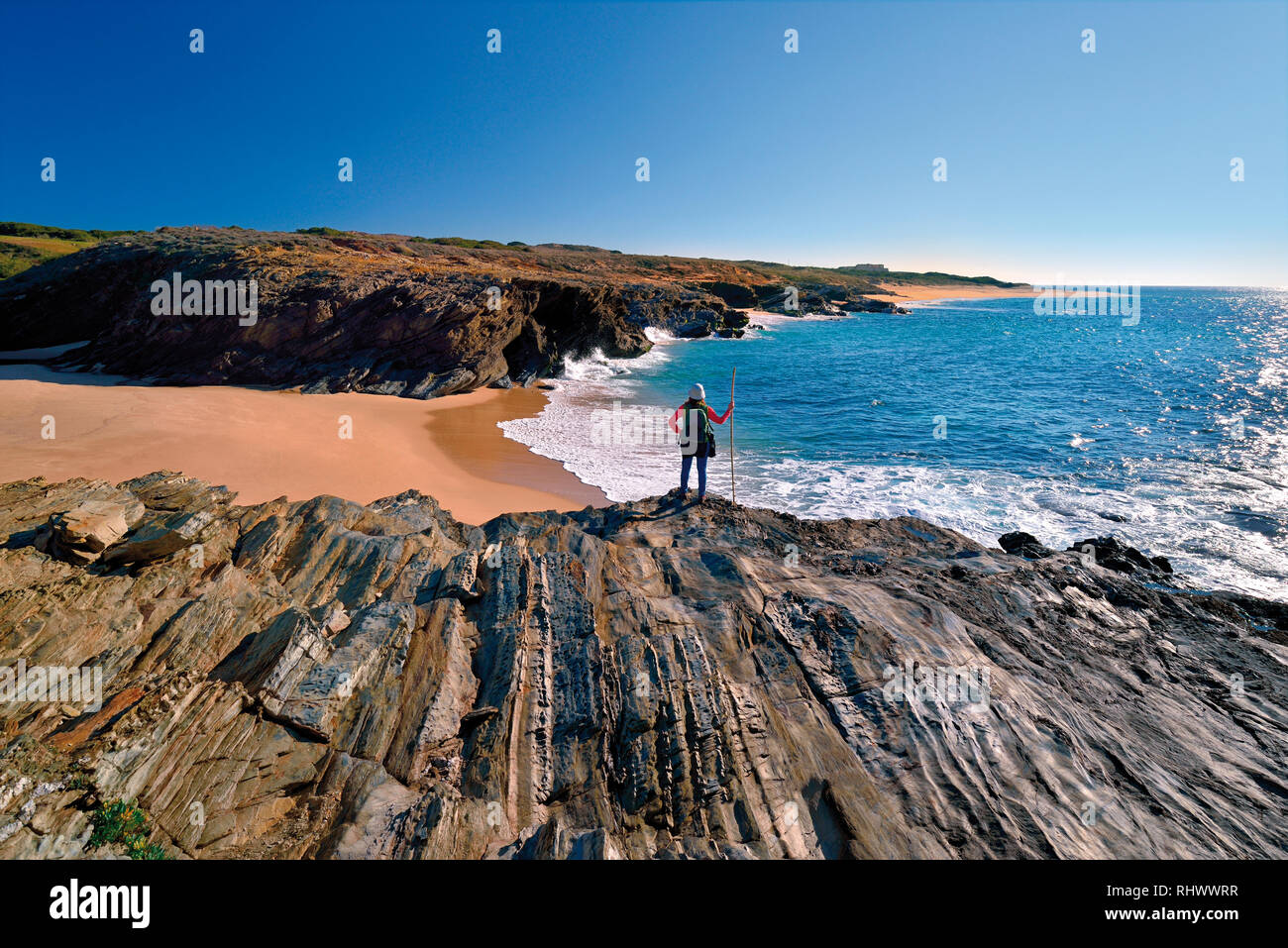 Female tourist with hiking outfit standing on a rocky cliff overlooking a wild sandy beach - Stock Image