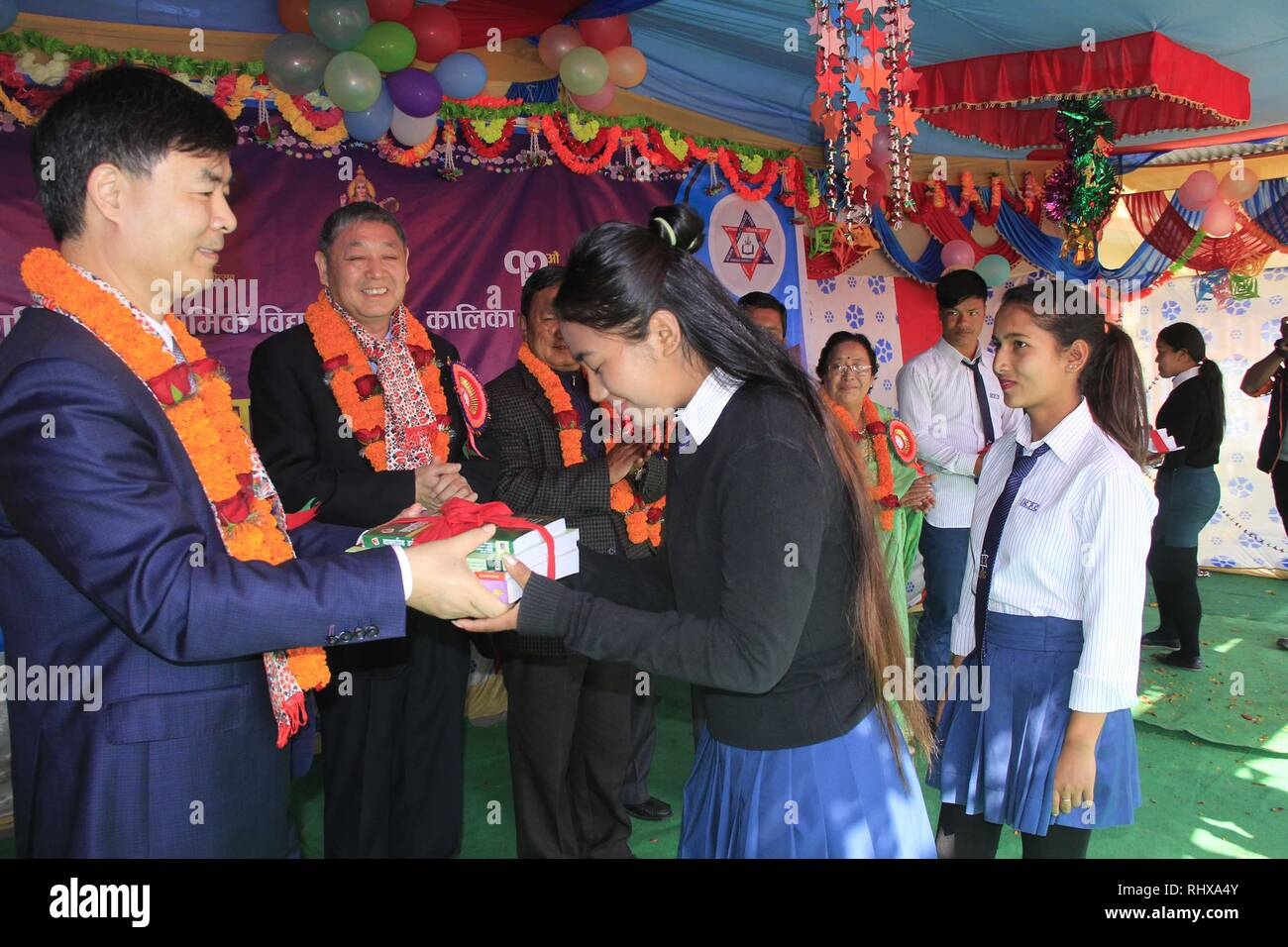 Pokhara, Nepal. 4th Feb, 2019. A representative of China CAMC Engineering Co. Ltd offers books to the students of Kalika Secondary School and Public College in Pokhara, Nepal, Feb. 4, 2019. The Chinese company made a donation of Rs one million (about 9,000 U.S. dollars) to the school, for students from poor families. China CAMC Engineering Co. Ltd is the contractor of the Pokhara International Airport, which is being built in the tourism hub Pokhara. Credit: Krishna Mani Baral/Xinhua/Alamy Live News - Stock Image