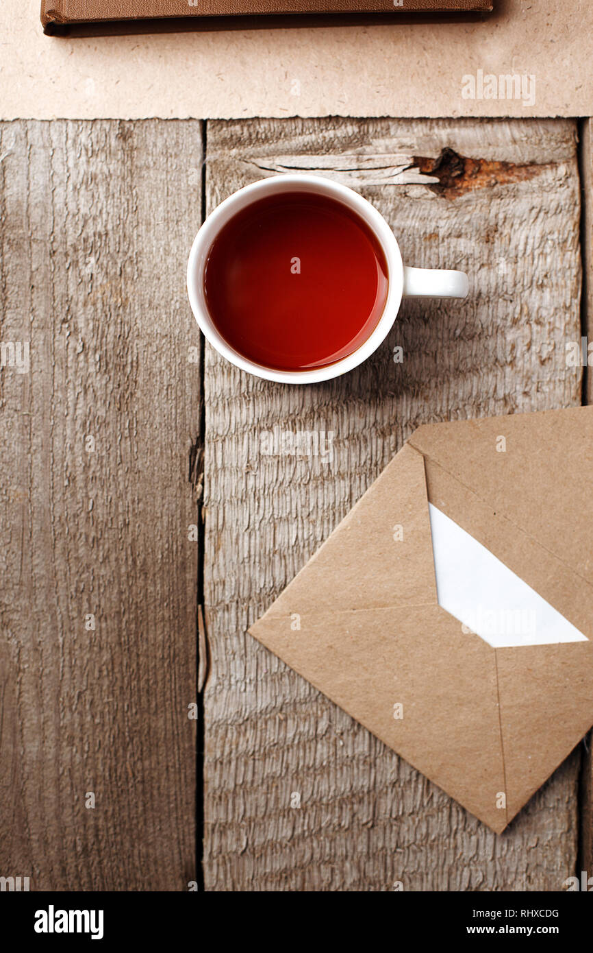 A cup of tea and envelope with a letter on vintage wooden background, stylish minimal teatime break or morning concept, top view, flat lay, copy space - Stock Image