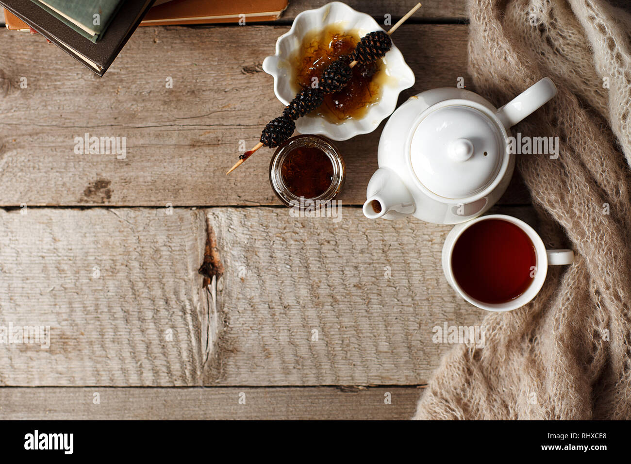 cup of tea with siberian sweetness - sugar cones, teapot and old books on wooden background, concept of cozy teatime, winter autumn weekend, leisure t - Stock Image
