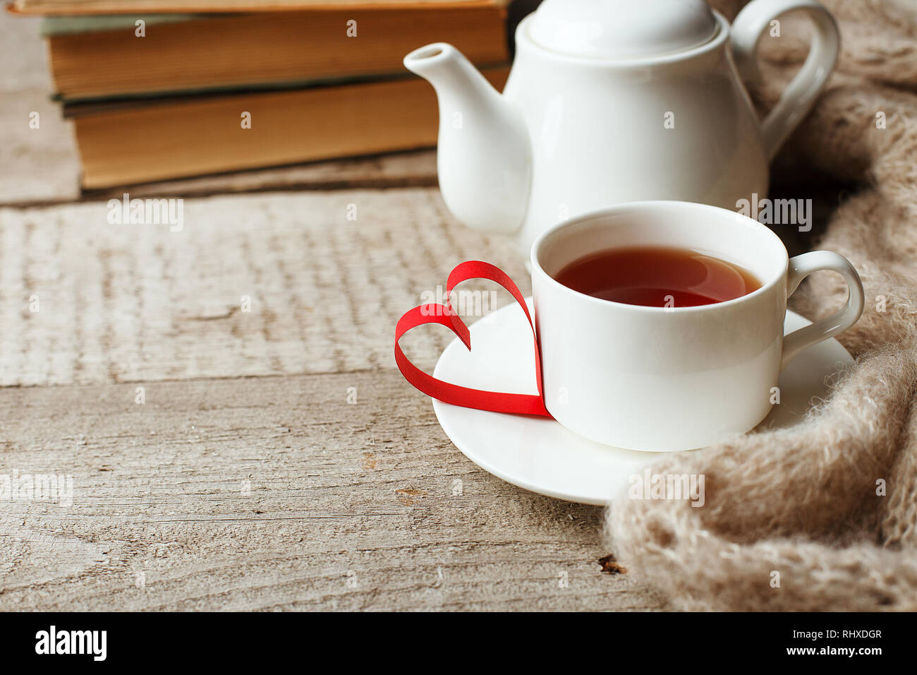 Valentines day concept with tea cup, papercraft heart and books on wooden vintage background, cozy weekend, hygge leisure concept - Stock Image
